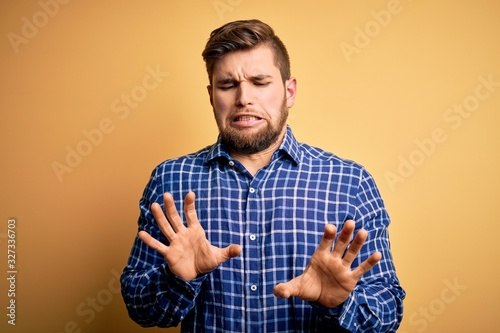 Young blond businessman with beard and blue eyes wearing shirt over yellow background disgusted expression, displeased and fearful doing disgust face because aversion reaction Canvas Print