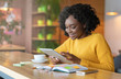 African businesswoman using digital tablet in cafe