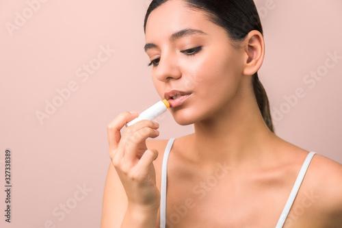 Photo beautiful young woman using lipstick to moisturize her lips