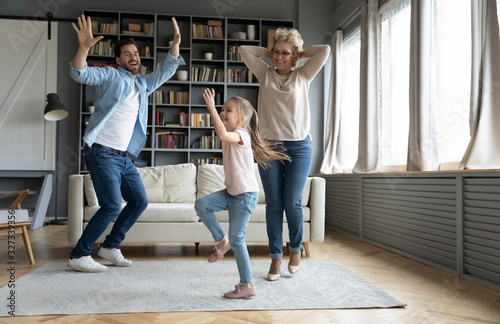 Overjoyed three family generations dancing at home - 327339356