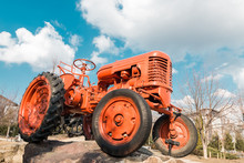 Old Red Tractor On Farm Over Blue Sky With Clouds