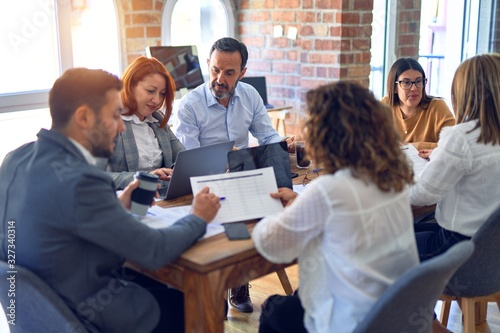 Group of business workers working together. Sitting on desk using laptop reading documents at the office