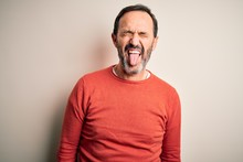 Middle Age Hoary Man Wearing Casual Orange Sweater Standing Over Isolated White Background Sticking Tongue Out Happy With Funny Expression. Emotion Concept.