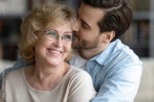 Fototapeta Loving adult son hug happy senior mother showing gratitude obraz