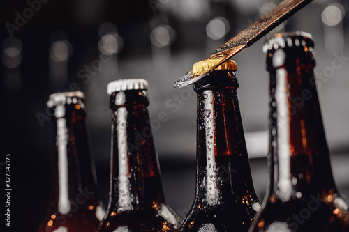 Canvas Row brown ice cold beer bottle with water drops and metal opener cap, dark backg