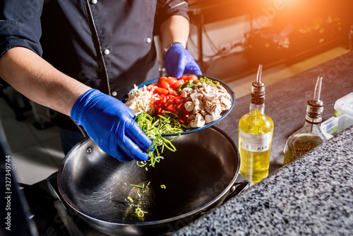 Chef cooking pasta with vegetables in pan Canvas Print