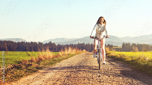 Fototapeta Young woman rides bicycle on dusty country road, afternoon sun shines at her, view from front obraz