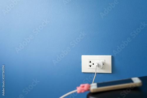 Fotografiet Adapter for mobile phone and electric plug on the dark blue wall.