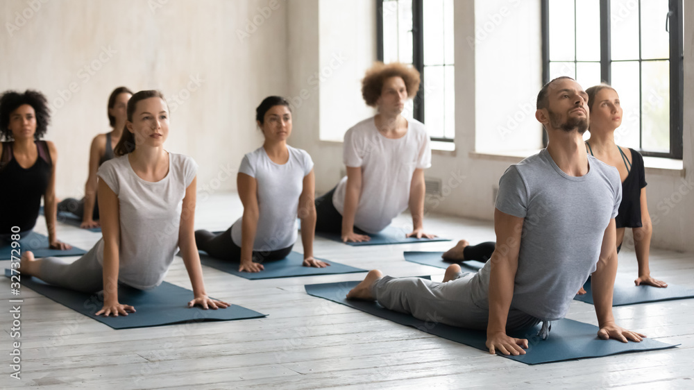 Fototapeta Male instructor and group of people performing Upward Facing Dog