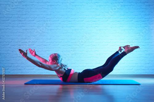 Obraz na plátně Flexible plastic girl doing pilates exercises on mat in yoga studio, body stretc