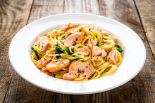 Pasta With Salmon And Spinach On Wooden Background