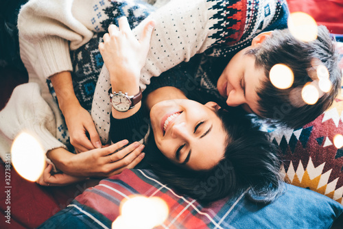 Happy young couple spending time together, hugging and lying on the bed Canvas Print