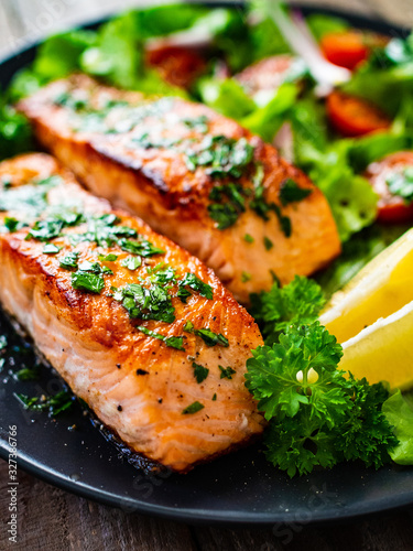 Foto Fried salmon steaks with vegetables on wooden table