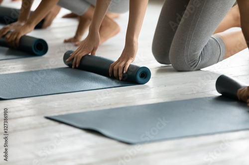 Fotomural Group of women fold up mats after yoga work out close up