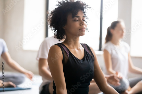 African female closed eyes do meditation practice with associates