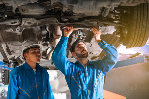 Mechanic in blue work wear uniform inspects the car bottom with a wrench with his assistant Canvas Print