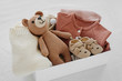 Leinwandbild Motiv Box with baby stuff and accessories for newborn on bed. Gift box with knitted blanket, clothes, socks, shoes and toy. Baby shower concept.  Flat lay, top view