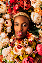 Close Up Beauty Portrait Of A Beautiful Young Woman's Face  With Pink Makeup Surrounded With Many Flower Blooms