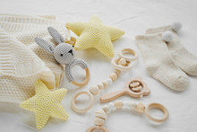 Knitted Toy Bunny, Yellow Stars And Wooden Teether For Newborn On White Bed. Gender Neutral  Baby Stuff And Accessories.