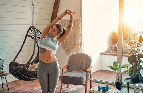 Photo Fitness woman exercising and stretching arms at home in the living room in sportswear