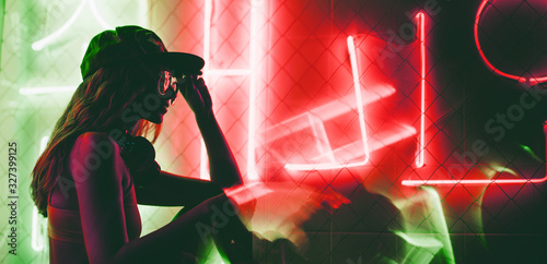 Canvas Print Sillhoutte of hip-hop girl in cap at the neon light