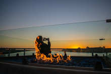 Young Woman Enjoying Sunset In Marina Del Rey In Winter With Fire Pit