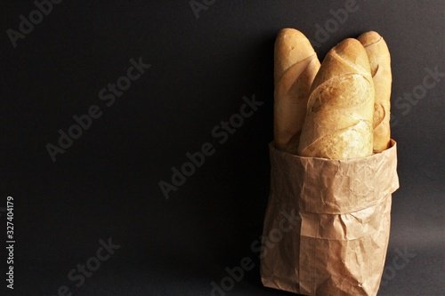 Valokuva Baguette bread in brown paper bag photo isolate on black front view