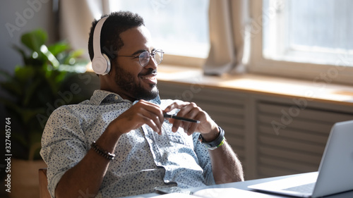 Photo Distracted from job study happy biracial man listening to music.