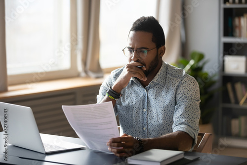 African american accountant employee reviewing research report.