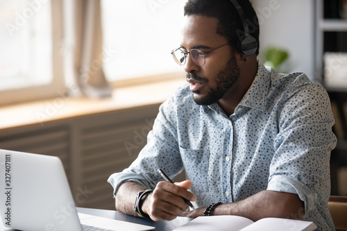 Focused young african american man watching educational lecture online Canvas Print
