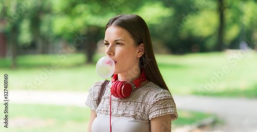 Photo Young lady blowing bubble with chewing gum