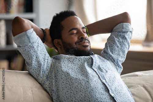 Peaceful carefree biracial guy alone napping on couch indoors. Wallpaper Mural