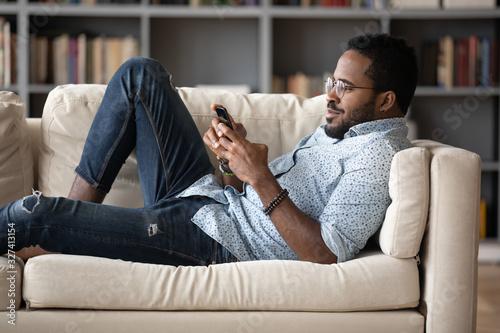 Obraz Young african american man lying on cozy sofa, playing games. - fototapety do salonu