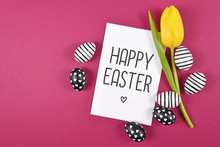 'Happy Easter' Text Card Surrounded By Black And White Easter Eggs And Single Yellow Tulip Spring Flower On Bright Pink Colored Background, Flat Lay With Copy Space On Left Side