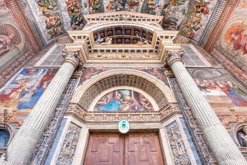 Wide low angle view of the colorful frescoed portal leading to the medieval cath Wallpaper Mural