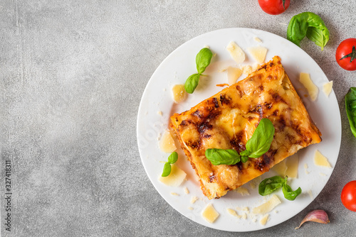 Fototapeta Meat lasagna with fresh basil and parmesan cheese in a plate on gray concrete background. top view with copy space obraz