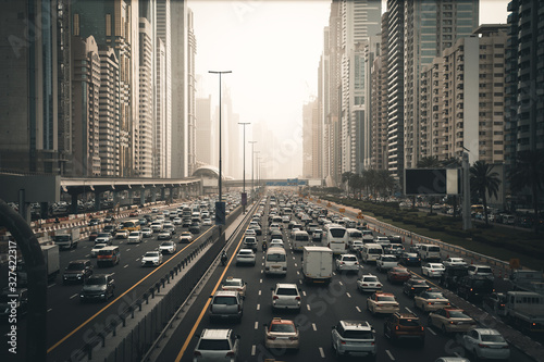 Fototapeta Rush hour with many cars on Dubai city road, traffic jam in downtown