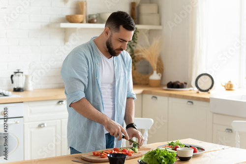 Fototapeta Young man stand in kitchen cooking salad for lunch obraz