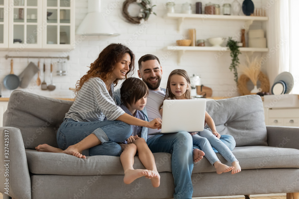 Fototapeta Happy family with kids sit on couch using laptop