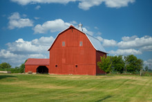A Beautiful, Very Large, Bright Red, Well Kept Barn By The Side Of The Road.  The Building Has A New Metal Roof, And A Side Building On The Left.