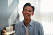 canvas print picture - Happy at work. Portrait of a happy young asian man in casual wear looking at camera and smiling while working in the creative office. Young designer in the creative working space