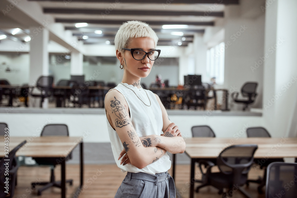 Fototapeta In her own style. Portrait of young and attractive blonde tattooed businesswoman in eyeglasses keeping arms crossed and looking at camera while standing in modern working space