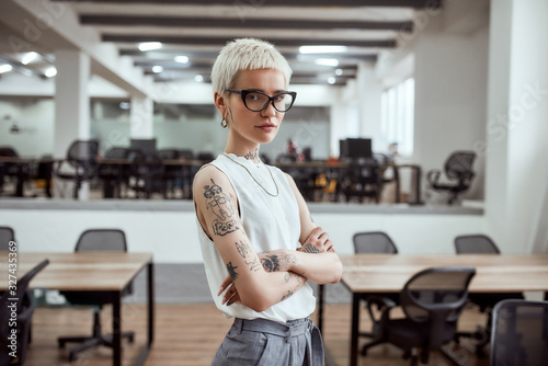 Fototapeta In her own style. Portrait of young and attractive blonde tattooed businesswoman in eyeglasses keeping arms crossed and looking at camera while standing in modern working space obraz