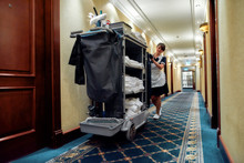 Cleaning At Its Finest. Full-length Shot Of Hotel Maid In Uniform Walking Along The Hall With Chambermaid Trolley. Room Service Concept.