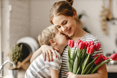 Fotografiet happy mother's day! child son gives flowers for  mother on holiday
