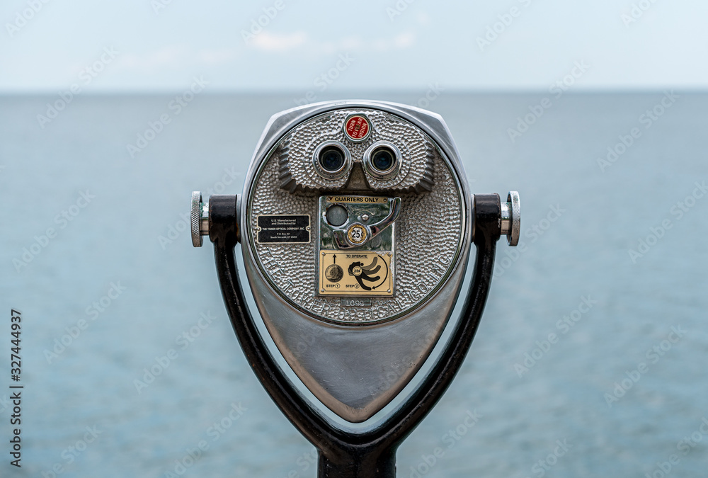 Fototapeta Binocular tower looking out over water towards the horizon line.