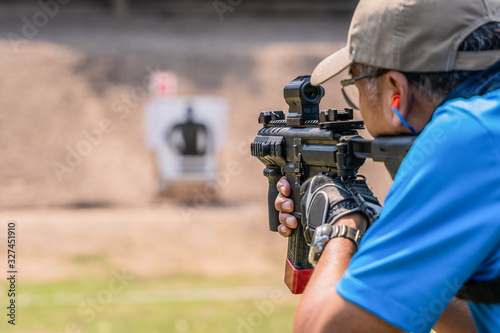 Fotografía selective focus of man holding and fire sub machine gun to target in gun shootin