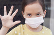 Asian little girl wearing medical face mask and making stop sign, self-quarantine, social distance, coronavirus, covid-19 virus outbreak epidemic pandemic, pm 2.5 air pollution and health concept