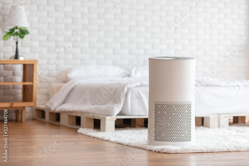 Obraz Air purifier in cozy white bedroom for filter and cleaning removing dust PM2.5 HEPA in home,for fresh air and healthy life,Air Pollution Concept - fototapety do salonu
