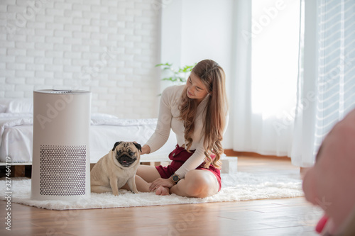 Obraz Woman playing with Dog Pug Breed and Air purifier in cozy white bed room for filter and cleaning removing dust PM2.5 HEPA in home,for fresh air and healthy life,Air Pollution Concept - fototapety do salonu